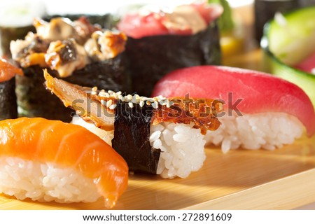 Japanese Cuisine - Sushi Set: Salmon, Conger and Tuna Sushi with Salad Leaf. Nigiri, Maki Sushi and Sashimi - stock photo