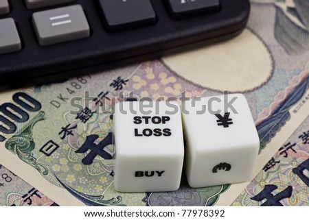 Japanese currency with calculator and dice showing STOP LOSS - stock photo