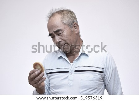 Japanese elderly male thinking by looking at sweets isolated