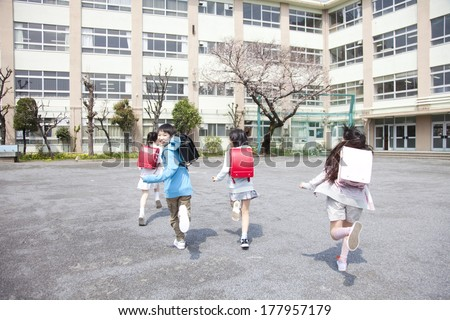 Japanese elementary students playing in the school yard - stock photo