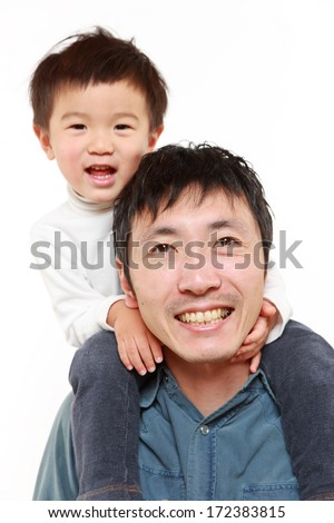 Japanese father giving his son piggy back - stock photo