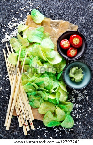 Japanese food background with potato chips and snacks with wasabi on black marble