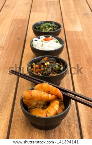 Japanese food composed with four black bowls with shrimps, rice noodles, kale (green cabbage), fried vegetables and asian chopsticks. Composition on a old styled wooden table. - stock photo