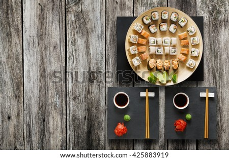 Japanese food restaurant, salmon sushi maki gunkan roll plate or platter set. Chopsticks, ginger, soy, wasabi. Sushi at black stone mat and rustic wood background. Top view, flat lay, copyspace - stock photo