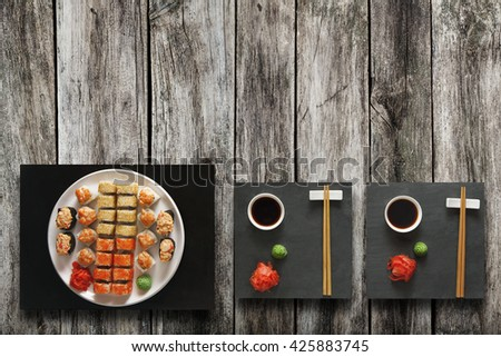 Japanese food restaurant, salmon sushi maki gunkan roll plate or platter set. Set for two with chopsticks, ginger, soy, wasabi. Sushi at black stone mat and rustic wood background. Top view, flat lay. - stock photo
