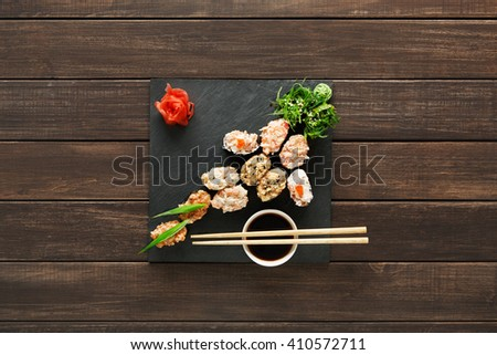Japanese food restaurant, sushi gunkan roll plate, platter set. Creative food. Set with chopsticks, ginger, soy, wasabi. Sushi at rustic wood background and black stone. Flat lay, top view.  - stock photo