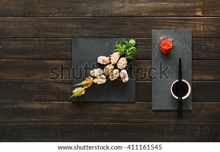 Japanese food restaurant, sushi gunkan roll plate, platter set. Creative food. Set with chopsticks, ginger, soy, wasabi. Sushi at rustic wood background and black stone. Flat lay, top view. Copyspace. - stock photo
