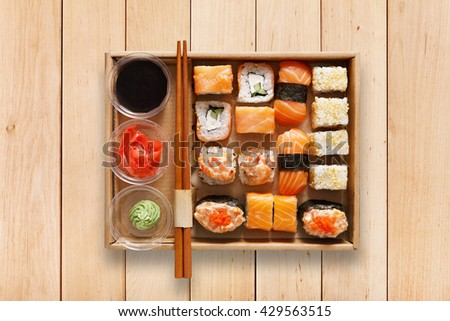 Japanese food restaurant, sushi maki gunkan roll plate or platter set. Chopsticks, ginger, soy sauce, wasabi. Sushi on wooden table background, take away, delivery box. Top view. - stock photo
