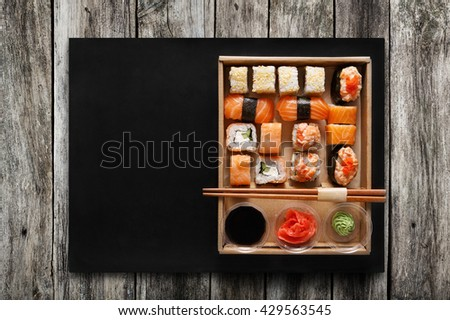 Japanese food restaurant, sushi maki gunkan roll plate or platter set. Chopsticks, ginger, soy sauce, wasabi. Sushi on rustic wood background and black mat, take away, delivery box. Top view. - stock photo