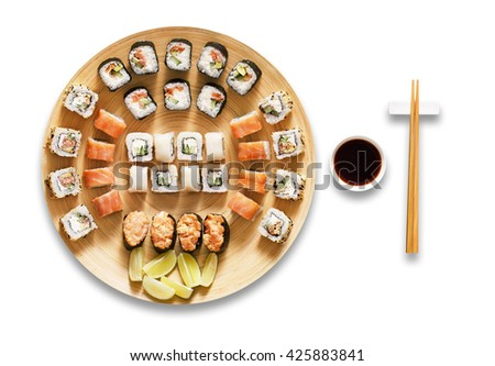 Japanese food restaurant, sushi maki gunkan roll plate or platter set. Chopsticks, ginger, wasabi and soy sauce. Sushi at bamboo round plate isolated at white background. - stock photo