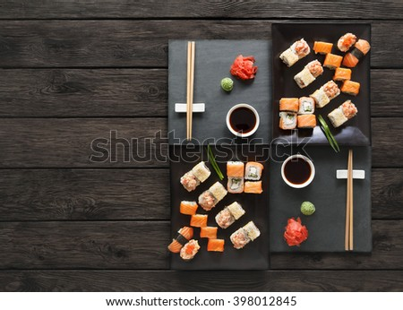 Japanese food restaurant, sushi maki gunkan roll plate or platter set. Copyspace with chopsticks, ginger and wasabi. Sushi at rustic wood background and black stone. Top view at black. Flat lay. - stock photo