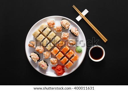 Japanese food restaurant, sushi maki gunkan roll plate or platter set. Free, copy space, chopsticks, ginger and wasabi. Sushi at white round plate, rustic wood background. Top view with soy sauce - stock photo