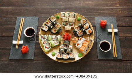Japanese food restaurant, sushi maki gunkan roll plate or platter set. Set for two with chopsticks, ginger, soy, wasabi. Sushi at rustic wood background and black stone. Bamboo plate at wood - stock photo
