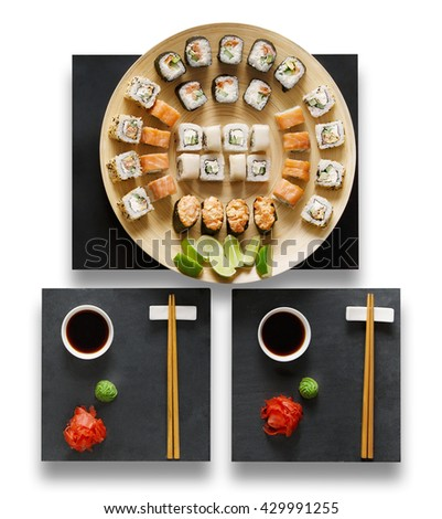 Japanese food restaurant, sushi maki gunkan roll plate or platter set. Set for two with chopsticks, ginger, soy sauce and wasabi. Sushi at black stone isolated at white background. Top view, Flat lay. - stock photo