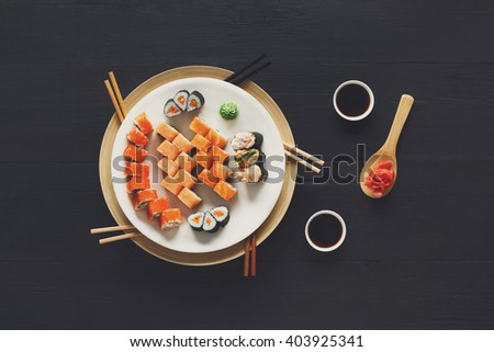 Japanese food restaurant, sushi maki gunkan roll plate or platter set. Set with colorful chopsticks, ginger, soy, wasabi. Sushi at rustic wood background and black stone. Top view at black - stock photo