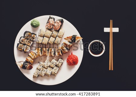 Japanese food restaurant, sushi unagi gunkan roll plate or platter set. Free, copy space, chopsticks, ginger and wasabi. Sushi at white round plate, rustic wood background. Top view with soy sauce - stock photo