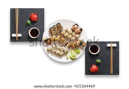 Japanese food restaurant, sushi unagi gunkan roll plate or platter set. Set for two with chopsticks, ginger, soy sauce and wasabi. Sushi at black stone isolated at white background. Top view, Flat lay - stock photo