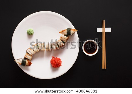 Japanese food restaurant, unagi sushi and roll plate set. One portion. Sushi with japanese fish eel, chopsticks, ginger and wasabi. Sushi at white round plate, black background. Top view, soy sauce. - stock photo