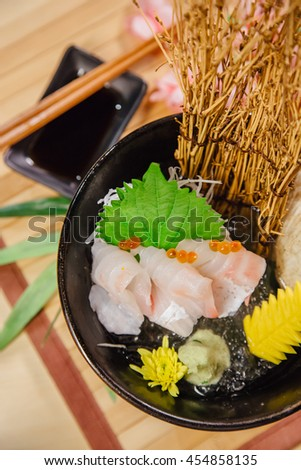 Japanese food Sashimi raw fish on ice hamachi or otoro in bow on wood table.