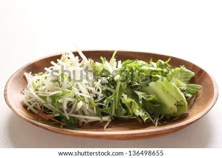 japanese food, sliced radish  and mizuna on wooden plate for salad image
