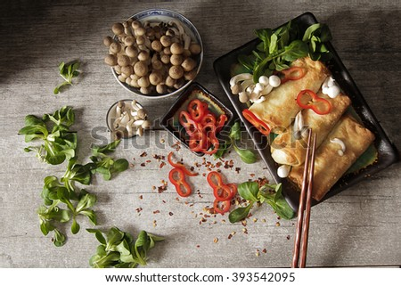 Japanese food style. Fried spring rolls with vegetables and shimeji mushrooms, on a gray background. Flat Lay. Top view. Chinese style