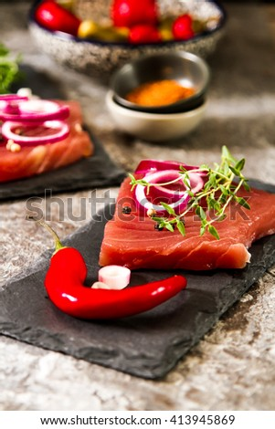 Japanese food. tuna steaks on a kitchen board with pepper and cucumber, tasty fish dinner - stock photo