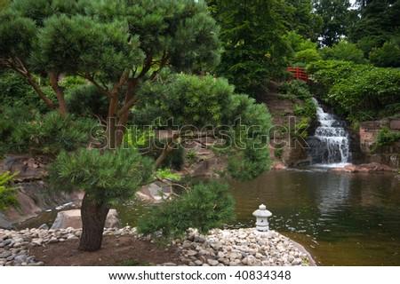 Japanese garden with bridge and waterfall - stock photo
