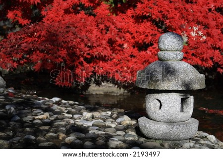Japanese garden with bright red maple and a stone statue. - stock photo