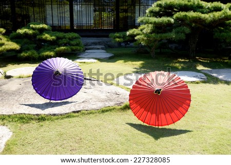 Japanese garden with traditional Japanese umbrella - stock photo