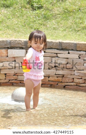 Japanese girl playing with water (1 year old) - stock photo