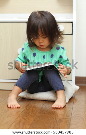 Japanese girl reading a picture book (1 year old)