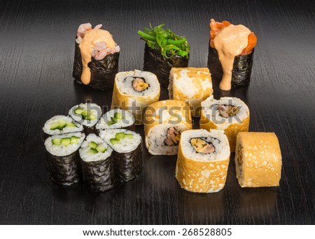 Japanese great sushi and roll set on a wooden black table - stock photo