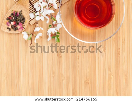 Japanese green tea and sakura branch over bamboo table with copy space - stock photo