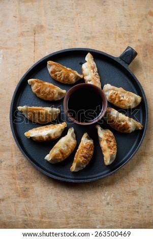 Japanese gyoza dumplings in a frying pan, rustic wooden surface - stock photo