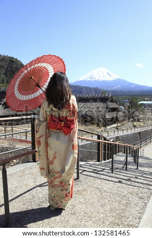 japanese kimono woman with traditional red umbrella with Fuji in the background - stock photo