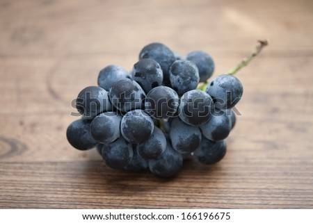 Japanese Kyoho grapes on wooden table with vignette