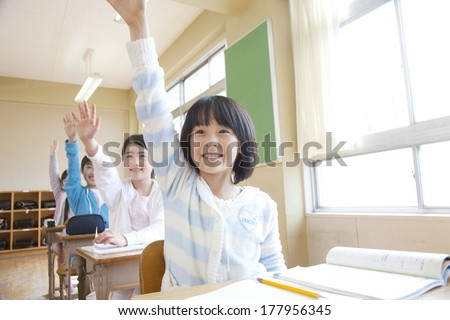 Japanese male and female elementary students raise their hands - stock photo