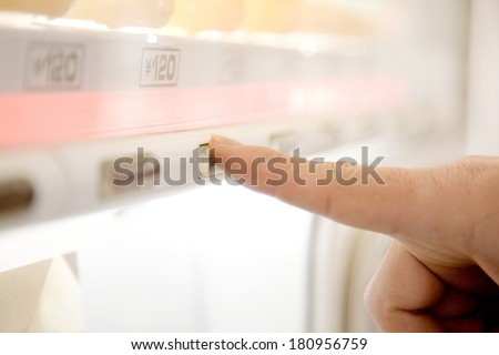 Japanese man buying drinks from a vending machine - stock photo