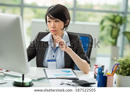 Japanese manager reading something on the monitor in the office - stock photo