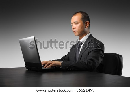 japanese manager working on laptop - stock photo