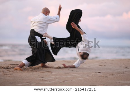 Japanese martial arts; master doing throwing technique, his partner in the air - stock photo