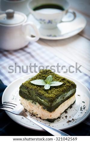 Japanese Matcha Green tea cake with a cup of matcha tea and milk jug, asian dessert - stock photo