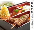 Japanese Meal in a Box (Bento) - Salad, Skewered Meat and Mashed Potato and Dessert - stock photo