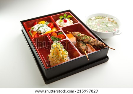 Japanese Meal in a Box - Salad, Skewered Meat and Mashed Potato and Dessert - stock photo