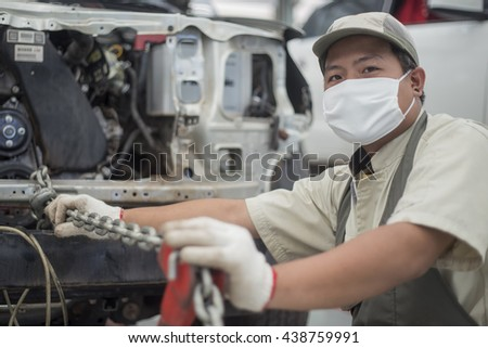 Japanese mechanic working on a car engine
