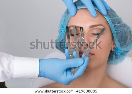 Japanese Method of Drawing Eyebrows, Pretty Brunette in Beauty Salon. The beautician is using a permanent tattoo pen with a blade, needles and black pigment. - stock photo