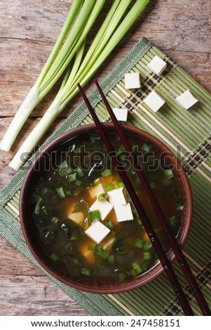 Japanese miso soup in a brown bowl on the table. vertical view from above