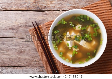 Japanese miso soup in a white bowl on the table. horizontal view from above  - stock photo