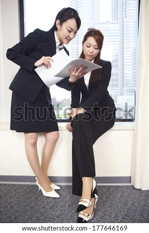 Japanese Office Ladies in the meeting while watching the material - stock photo