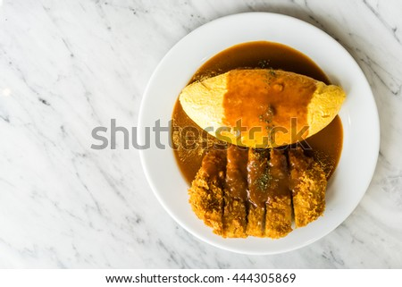 Japanese Omu Rice (fried rice with chicken and tomato sauce wrapped in egg omelet) with pork tonkatsu (Japanese fried pork cutlet) topped with Demiglaze sauce - stock photo